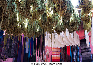 Dyed and drying wool in Medina in Marrakech, Morocco with scarves in the background