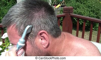 Dying Grey Hair Outside - Man is dying grey hair in the...