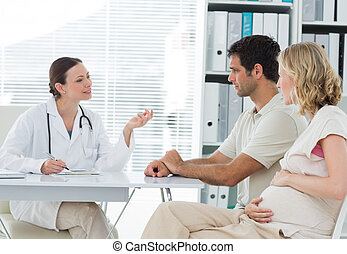 Dynaecologist discussing with expectant couple - Female...