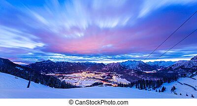 dynamic clouds over valley at winter night in tirol mountains