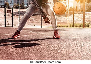 Nice young man holding a basketball ball