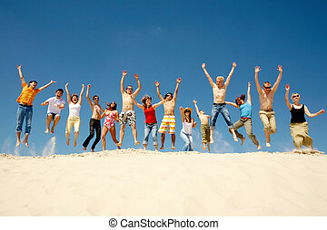 Dynamic people - Crowd of friends jumping on sandy beach...