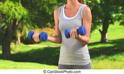 Dynamic woman using dumbbells in a park