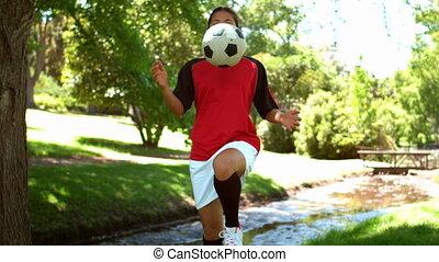 dziewczyna, grając piłkę nożna, w parku