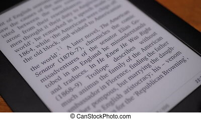 E-book Screen with Changing Text. Close-up. Page Turning. Electronic Ink Display.