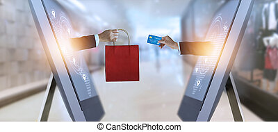 e-commerce, hand holding shopping bag and credit card from...