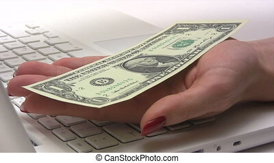 E-Commerce - Woman receiving money in front of her computer....