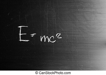 E equals mc squared drawn with white chalk and copy space on blackboard