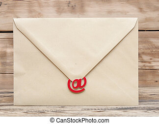 E-mail symbol and blank brown envelope on old wooden background . concept of E-Mail