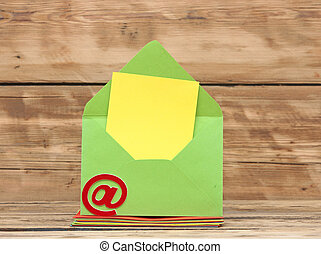E-mail symbol and colorful envelopes on old wooden background. concept of E-Mail