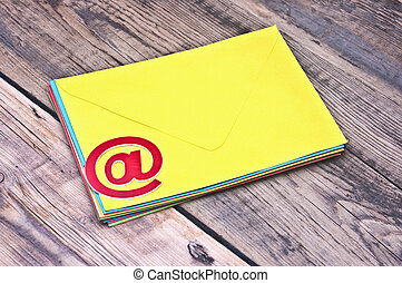 E-mail symbol and pile colorful envelopes on old wooden background