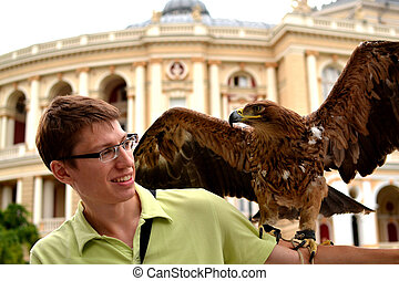 Eagle sits on the young man's shoulder
