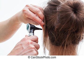 Ear examining, isolated - Ear examining with an otoscope,...