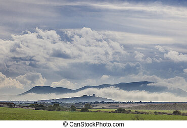 scenery of cereals fields and little town with castle between the fog
