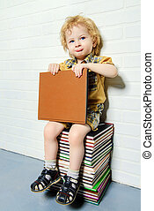 early child development - Cute little boy sitting on a stack...