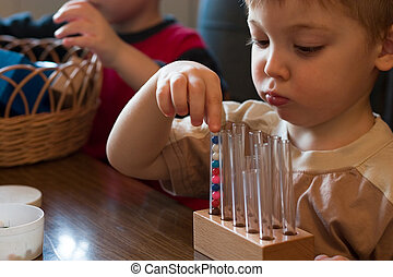early education - little boy playing with balls and vials in...