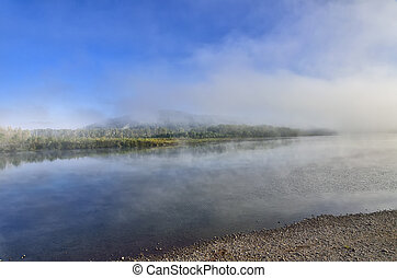 Early foggy morning over the river - beautiful summer landscape