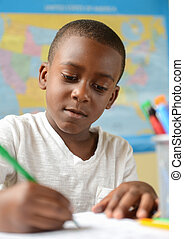 A young African American boy in school doing his work