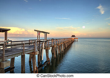 Early moonset and sunrise over the Naples Pier on the Gulf Coast of Naples, Florida