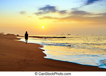 Early morning beach - Young woman walk on an empty wild ...