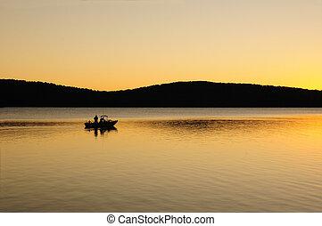 Early morning fishing boat on a lake at dawn