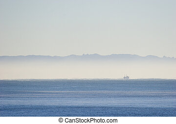 Early morning mist - Mist over the ocean with a fishing boat