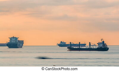 Early morning scene of cargo ships and tankers anchored off...