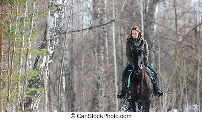 Early spring. A smiling woman riding a horse in the forest....