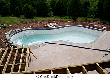 Creating a concrete swimming pool in residential back yard with surrounding deck and being filled with water
