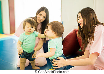 Good looking children therapist and a baby girl having fun in front of a mirror in an early stimulation and development center