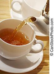 early tea - flowing golden tea into cup