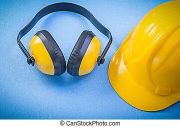 Earmuffs building helmet on blue background construction concept