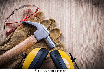 Earmuffs hammer safety gloves and goggles on wood board