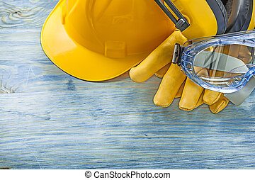 Earmuffs safety gloves hard hat goggles on wooden board construc