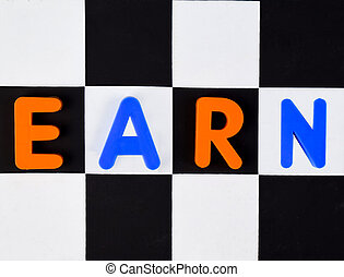 Earn word written with different colored letter blocks on a black and white background