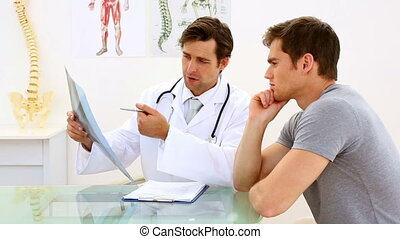 Earnest doctor discussing xray with his patient in his...