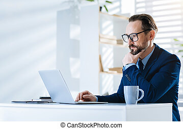 Earnest pensive man working with laptop