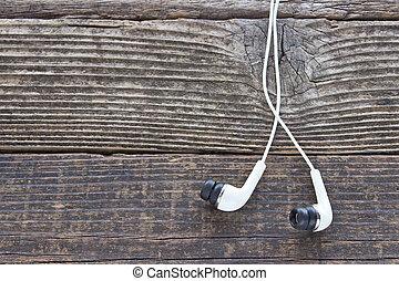 Earphones on wooden background