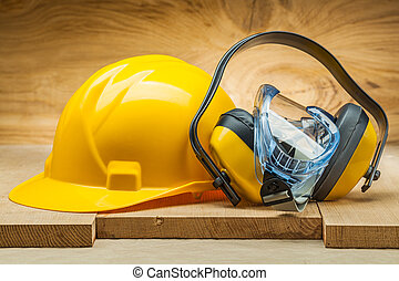 earphones with blue goggles and yellow helmet. safety tools