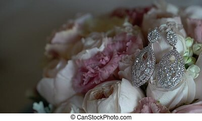Earrings and bouquet with roses closeup