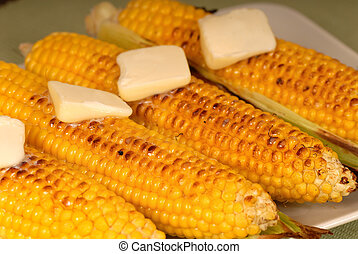 Ears of roasted corn with butter - Four ears of roasted corn...