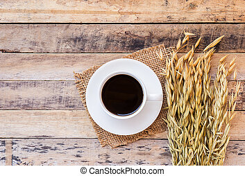 Ears of wheat and cup of coffee on a wooden table