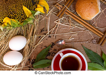 Ears of wheat , tea , cup, sunflower , eggs and bread on burlap