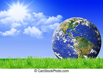 blue planet Earth on green grass and blue sky background