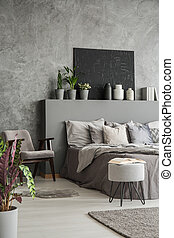 Earth colors bedroom interior with a big bed, an armchair, a footstool in a modern cozy hotel. Black painting on a textured grey wall. Real photo.