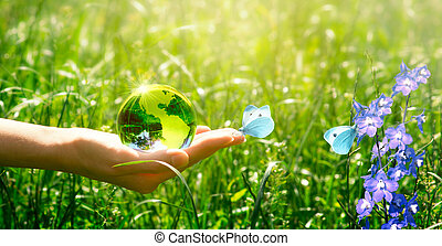 Earth crystal glass globe and butterfly in hand on grass and bluebell flowers background. Saving environment and clean green planet concept. Card for World Earth Day concept.