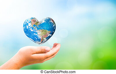 Earth Day concept: hand hold Earth in Heart shape on Natural...