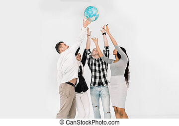 Earth day, education, travel and geography concept - happy four multiethnical students or friends throwing up the earth globe while standing on the white background