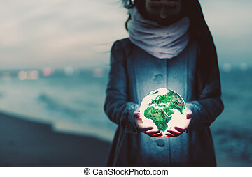 Earth globe glowing in woman's hands on the beach at night.