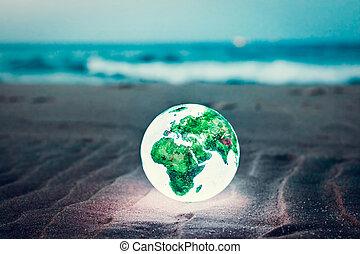 Earth globe glowing on the beach at night